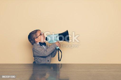 istock Young Nerd Boy Yells into Megaphone 992091590