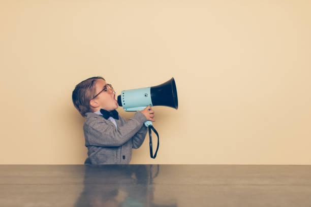 young nerd boy yells into megaphone - megafono foto e immagini stock