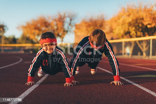 A young team of nerd boys are dressed in retro track suits and headbands attempt pushups on the running track ready to live a healthy lifestyle. They are eager to stretch and exercise while finding their inner mojo. Image taken in Tempe, Arizona.