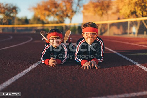 A young team of nerd boys are dressed in retro track suits and headbands lay down on the running track ready to live a healthy lifestyle. They are eager to stretch and exercise while finding their inner mojo and strength. Image taken in Tempe, Arizona.