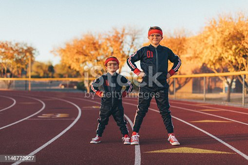 A young team of nerd boys are dressed in retro track suits and headbands stand on the running track ready to live a healthy lifestyle. They are eager to stretch and exercise while finding their inner mojo. Image taken in Tempe, Arizona.