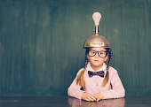 A young female nerd girl sits in a classroom setting with a thinking cap on her head. She has a blank look on her face as the light bulb is not turning on and she is not getting ideas. She is wearing a pink cardigan and bow tie. Learning is fun when you have ideas.