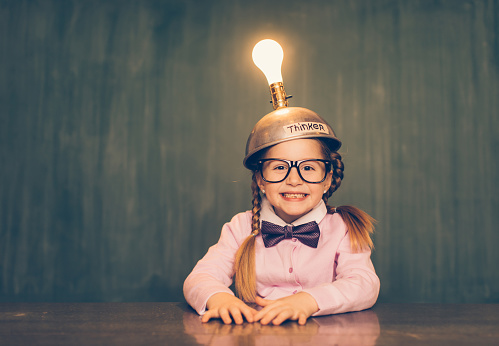 A young female nerd girl sits in a classroom setting with a thinking cap on her head. She has an excited look on her face as the light bulb is turned on and she is getting loads of ideas. She is wearing a pink cardigan and bow tie. Learning is fun when you have ideas.