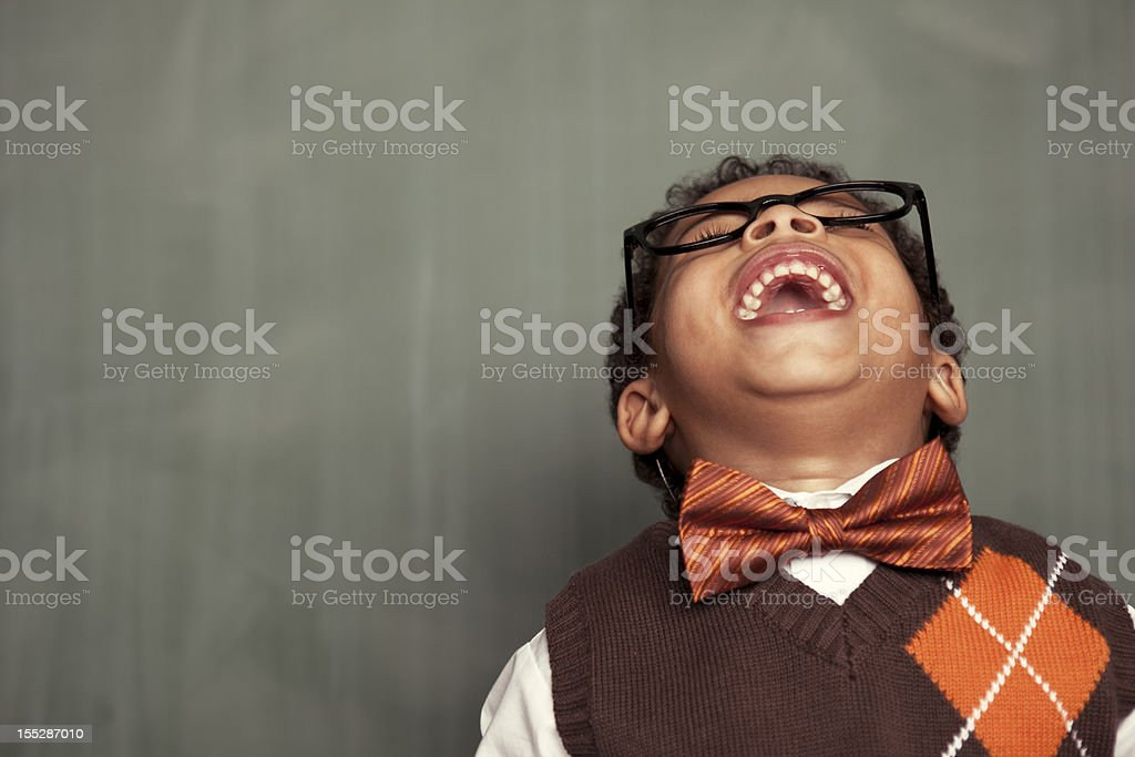 Young nerd in glasses leaning back and laughing stock photo
