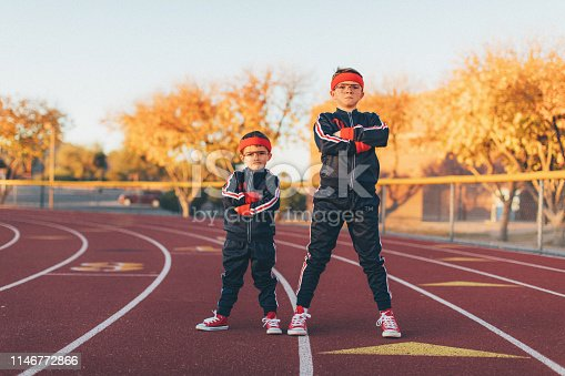 A young team of nerd boys are dressed in retro track suits and headbands stand on the running track ready to out exercise the competition. They are eager to stretch and exercise while finding their inner mojo. Image taken in Tempe, Arizona.