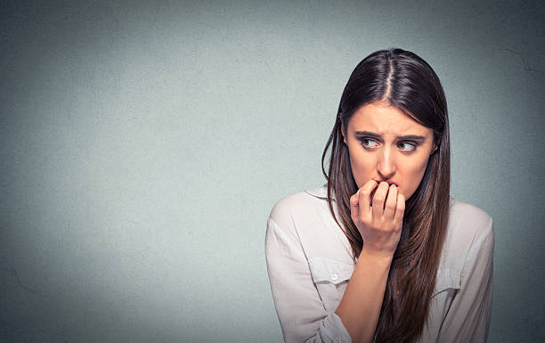 young nervous woman biting fingernails craving or anxious - anxiety stock photos and pictures