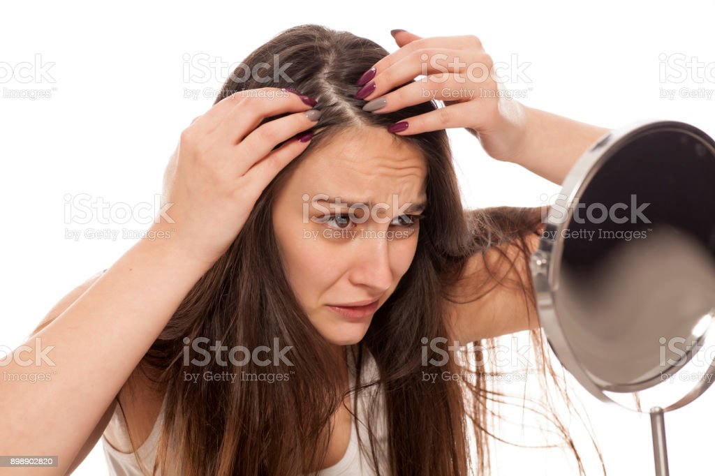 young nervous woman looks at her hair in the mirror stock photo