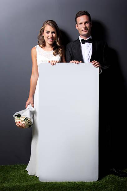 junge frisch verheiratet paar holding whiteboard - hochzeitskleid marken stock-fotos und bilder