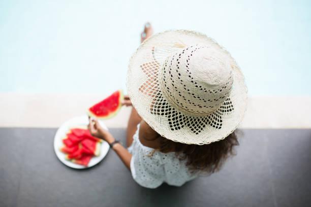 Young Nice Woman Eating Watermelon on Pool Edge stock photo