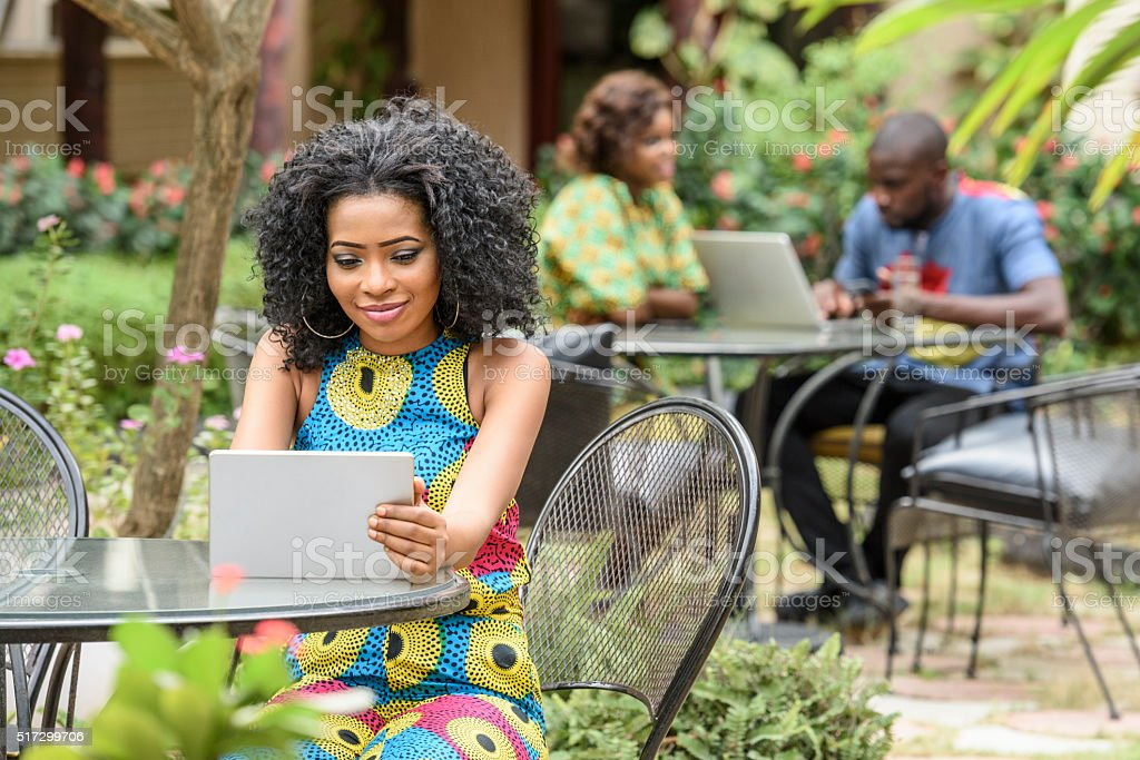 Young Nigerian woman using tablet in cafe stock photo