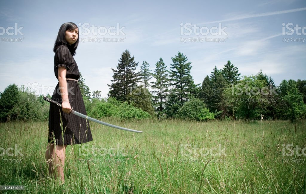 Young Ninja Warrior Girl In Field with Drawn Katana Sword royalty-free stock photo