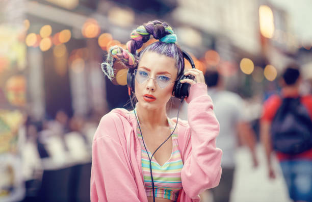 Young nonconformist girl listening music in headphones on the crowded streets. Blurred urban background stock photo