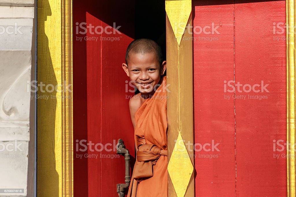 Young Novice monk smile in monastery the big window stock photo