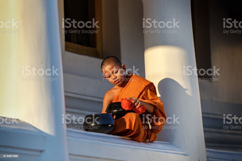 Young Novice monks sit cleaning alms bowl in monastery stock photo