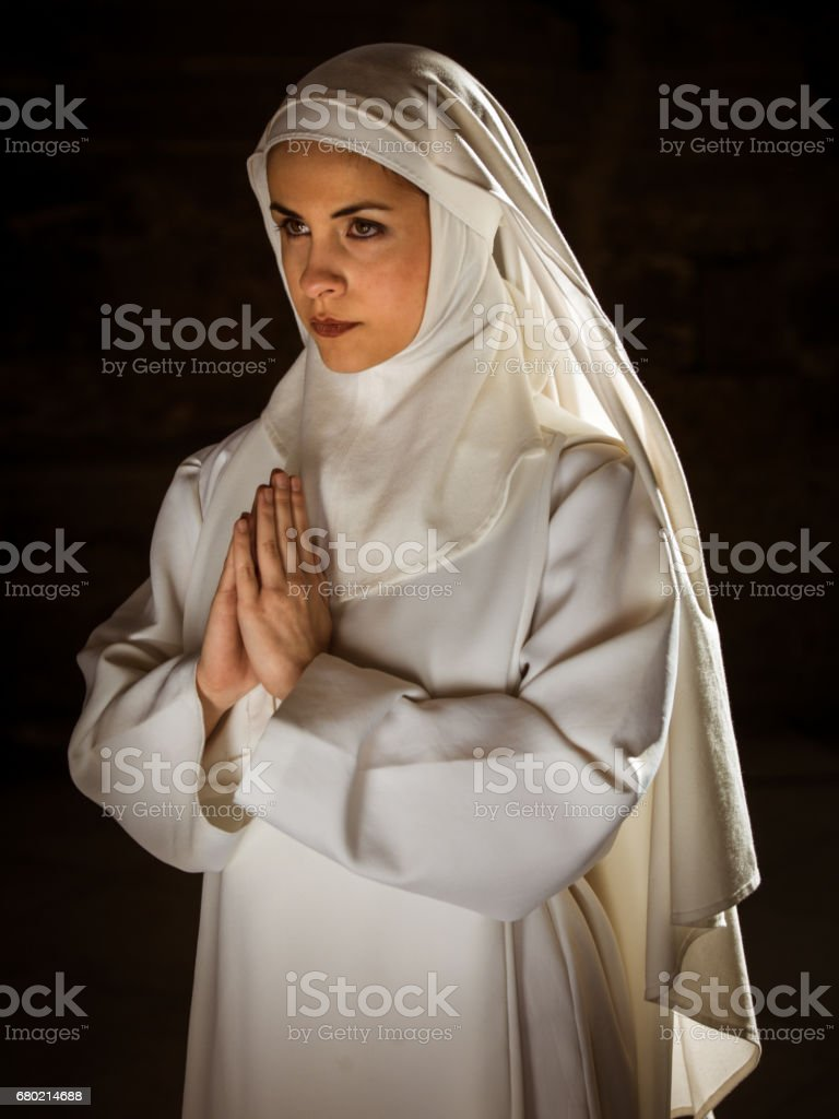Young Nun Praying inside Cathedral stock photo