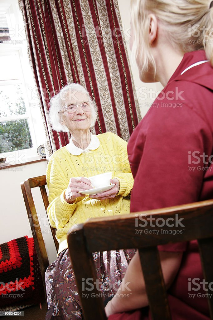 young nurse and senior woman chatting in a care home royalty-free stock photo