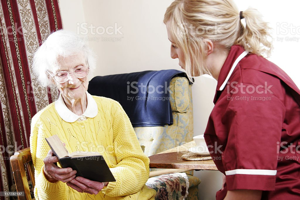 young Nurse and senior woman reading bible in care home royalty-free stock photo