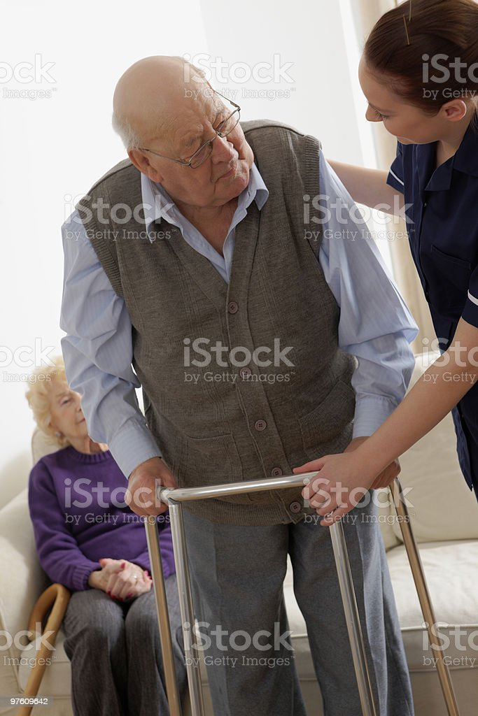Young nurse assisting a senior citizen with his walking frame royalty-free stock photo