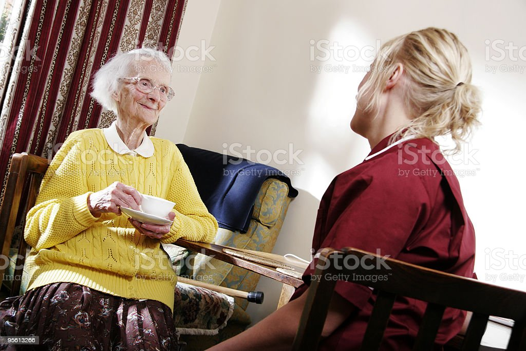 young Nurse chatting to elderly woman in a care home royalty-free stock photo