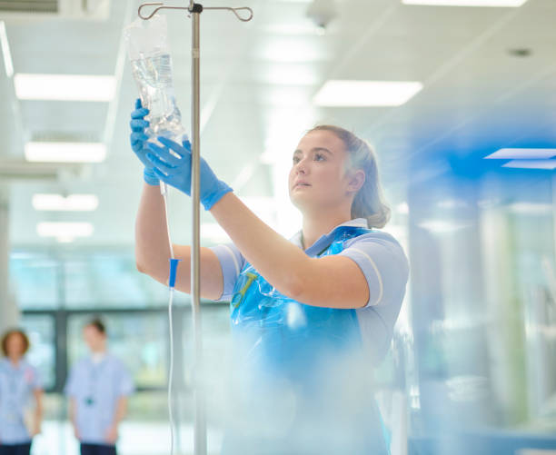 young nurse checks IV drip stock photo