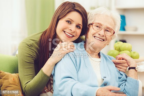 144362548istockphoto Young nurse embracing a happy senior woman 521512635