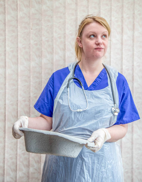 young nurse emptying bed pan stock photo
