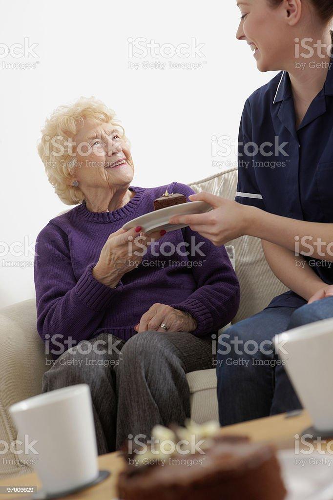 young nurse giving chocolate cake to senior woman royalty-free stock photo