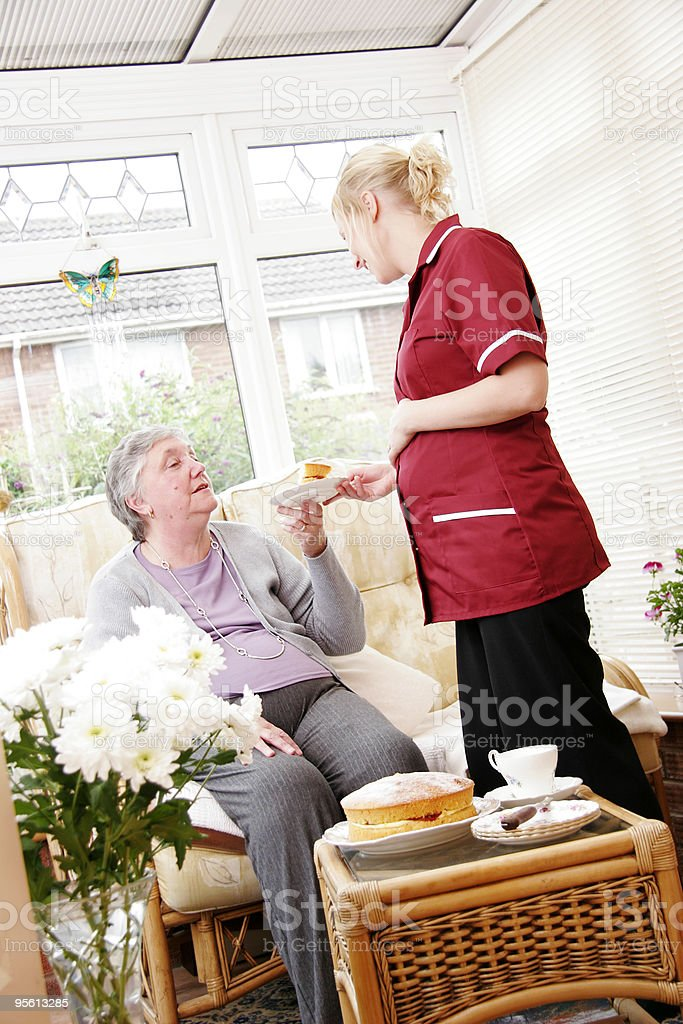 young Nurse having tea with senior woman in care home royalty-free stock photo