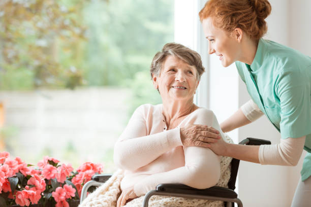 Young nurse helping an elderly woman in a wheelchair. Nursing home concept Young nurse helping an elderly woman in a wheelchair. Nursing home concept paraplegic stock pictures, royalty-free photos & images