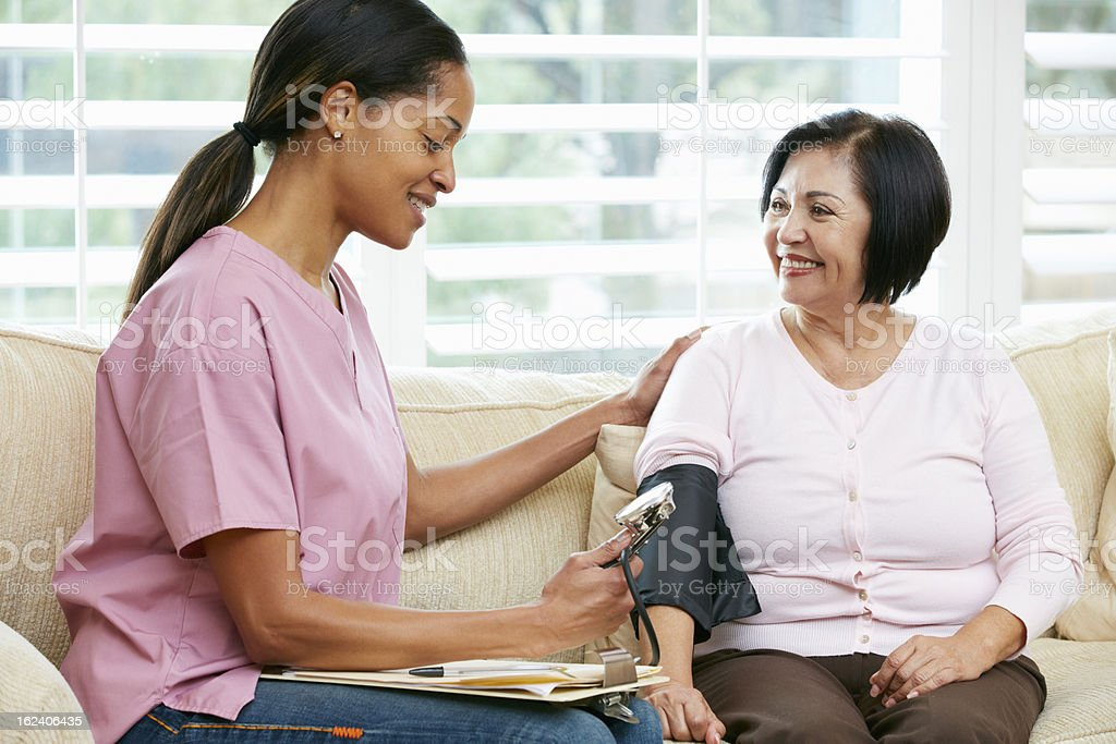 Young nurse making a home visit to a female senior patient stock photo