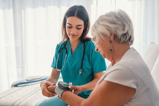istock Young nurse measuring blood pressure of elderly woman at home 1011191058