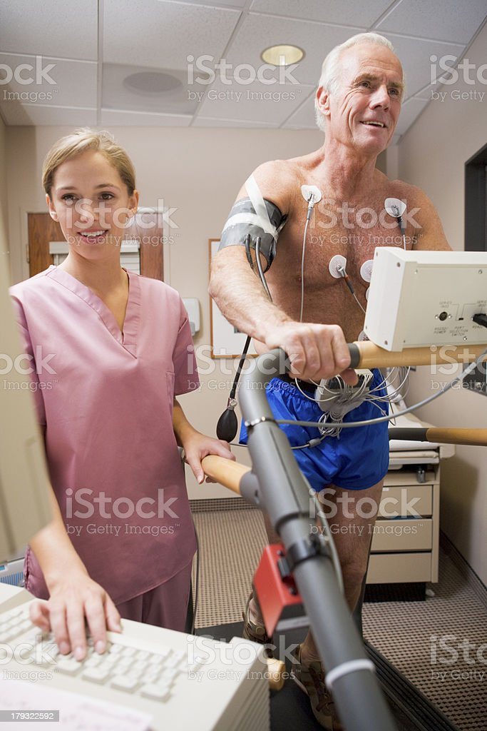 Young nurse observing elderly patient during health check royalty-free stock photo