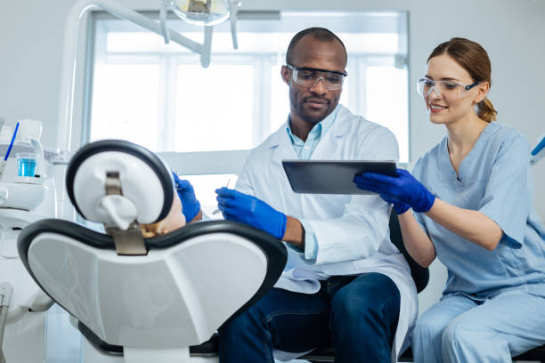Young nurse showing email on tablet to dentist examining patient stock photo