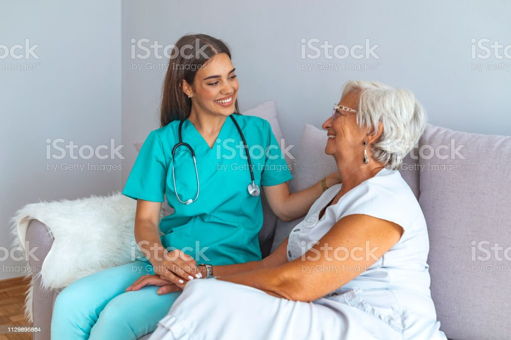 Young nurse spending time with happy elder patient in nursing home....