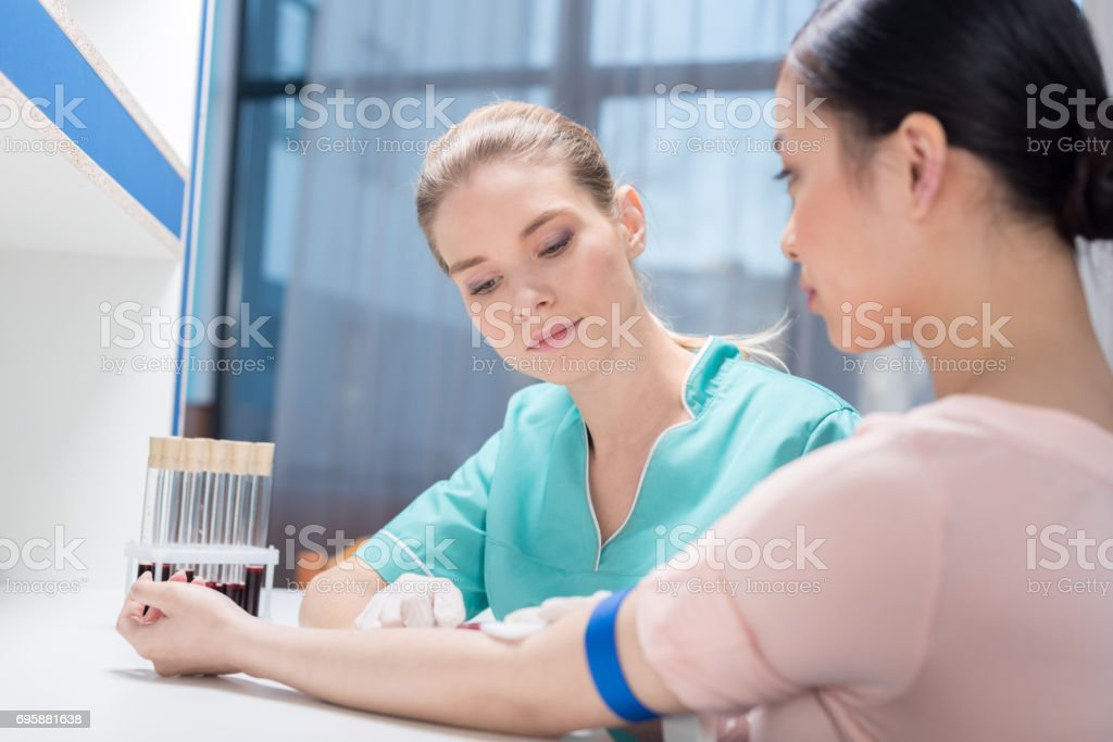 young nurse taking blood sample from patient at laboratory stock photo