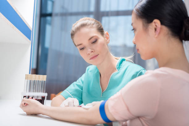 young nurse taking blood sample from patient at laboratory - blood testing stock pictures, royalty-free photos & images