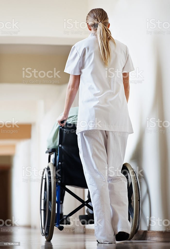 Young nurse taking  patient in a wheelchair royalty-free stock photo