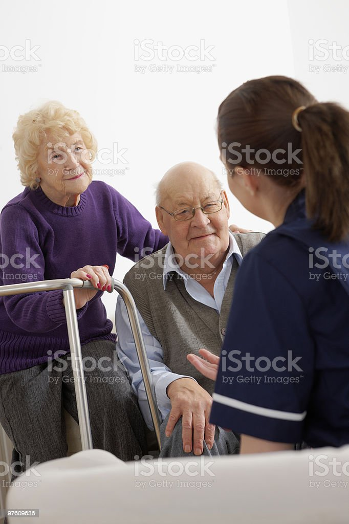Young nurse talking with senior couple Indoors royalty-free stock photo