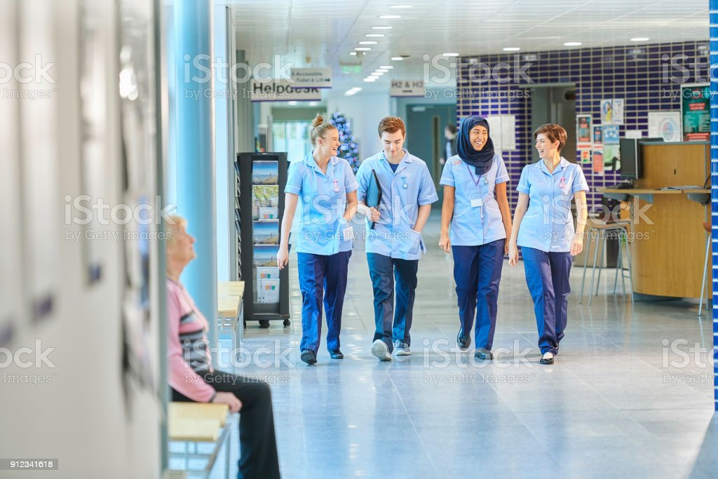 young nurses chatting on the way to ward stock photo