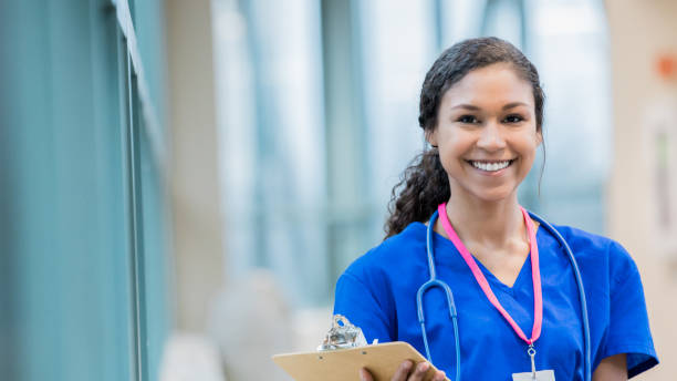 Young nursing student smiling and holding clipboard stock photo