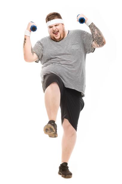 junge übergewichtige mann mit hanteln mit gesichtsausdruck, isoliert auf weiss - gymnastik tattoo stock-fotos und bilder