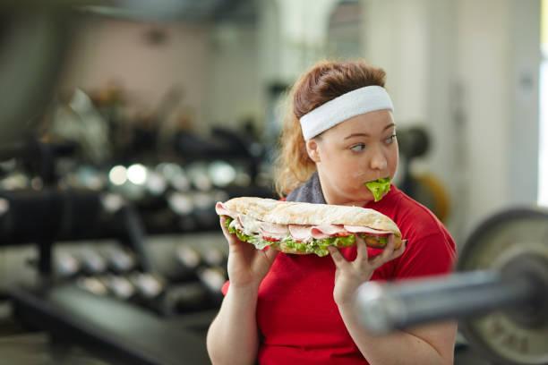 young obese woman hiding secret obsession with food - gewicht schnell verlieren stock-fotos und bilder