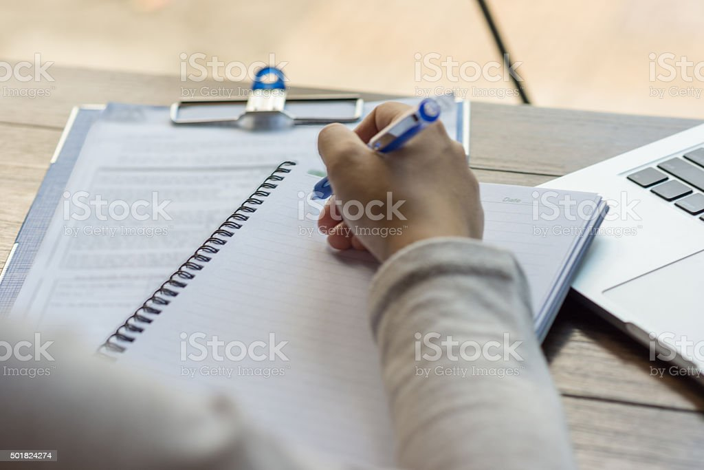 Young office employee writing weekly report to her boss stock photo