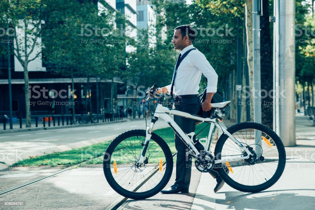 Young Office Worker with Bike Crossing Tram Line stock photo
