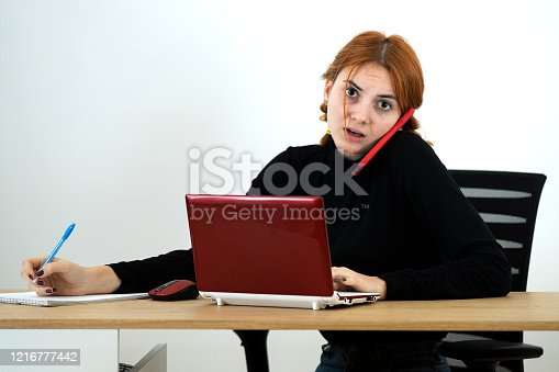 Young office worker woman talking on a cell phone sitting behind working desk with laptop computer and notebook.