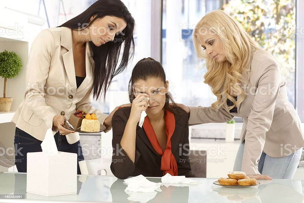 Young office workers comforting crying colleague royalty-free stock photo