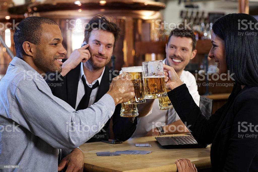 Giovane ufficio lavoratori di brindare con la birra al pub - foto stock