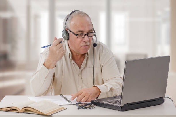 Young old man working as an online freelance teacher stock photo