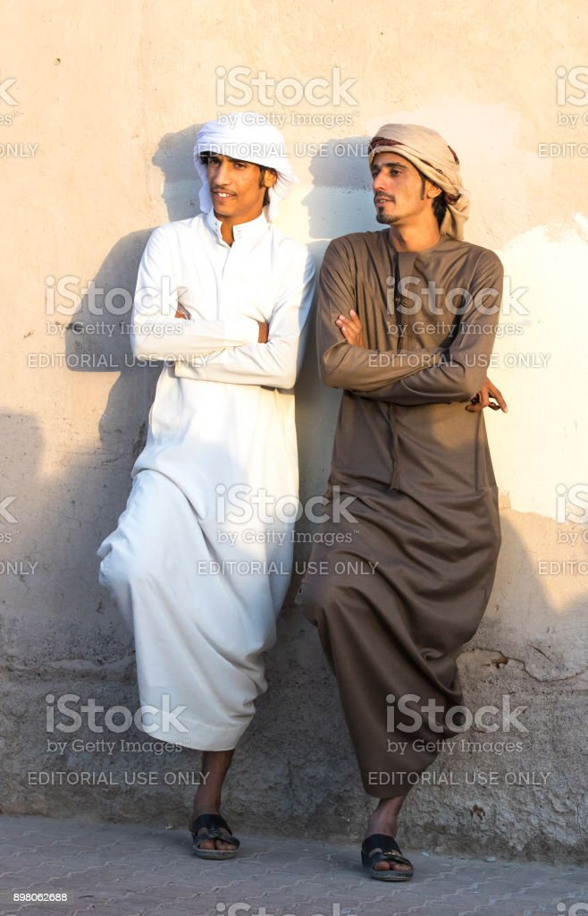 young omani men in traditional clothing socialising at a market stock photo