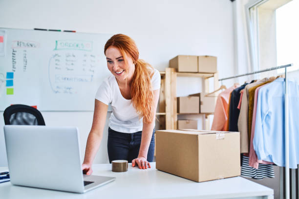 Young online business owner looking at laptop while preparing deliveries for clients Young online business owner looking at laptop while preparing deliveries for clients e commerce stock pictures, royalty-free photos & images